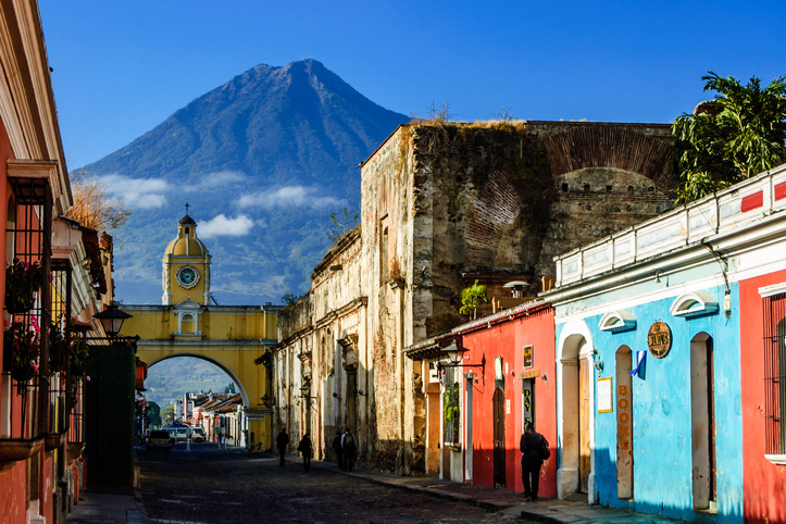 Antigua, Guatemala - March 11, 2012: Locals walk to work along Antigua's famous cobblestoned street lined with painted shops, restaurants & hotels. Agua volcano looms behind Santa Catalina Arch, a landmark in this Spanish colonial town & UNESCO World Heritage Site. Originally the arch allowed nuns to pass from one side of Santa Catalina convent to the other without going outside. Ruins of the convent remain to the right of the arch.